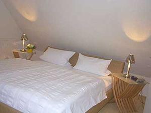 Das Schlafzimmer des Appartments. Doppelbett mit Nachtschränkchen.
