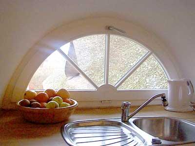 Der Küchenbereich der Ferienwohnung liegt an einer Gaube mit einem kleinen Sprossenfenster mit idyllischem Blick auf das Reetdach.